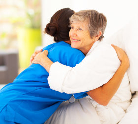 caregiver assists the elderly woman on bed
