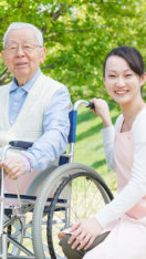 elderly man and a caregiver at park